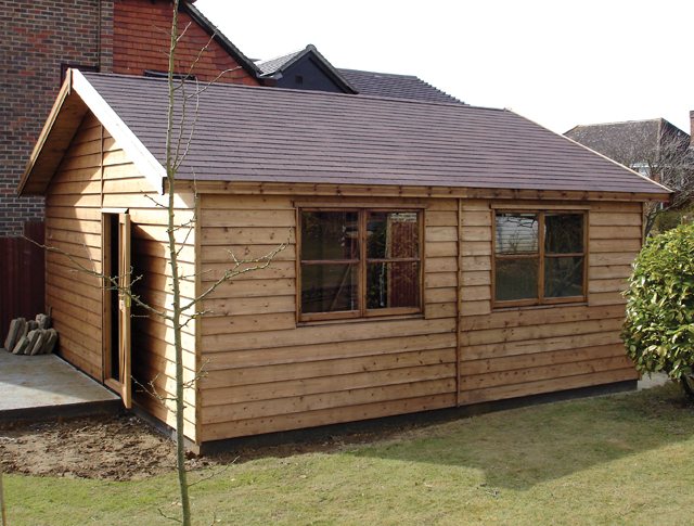"<p id=""boldtitle"">Gable Garage </p>18' x 18' (5490mm x 5490mm) gable garage.   Shown with optional prepared weatherboard cladding, personal door, four Gainsborough windows and brown felt tiled roof.<br/>"