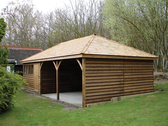 "<p id=""boldtitle"">Hip roofed Carport </p>28' 6"" x 15' (8686mm x 4575mm) hip roofed tractor/carport with workshop to one side.  Shown with optional sawn weatherboard cladding.<br/>"