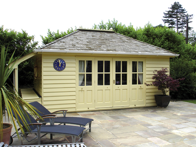 "<p id=""boldtitle"">Hip Roofed Summerhouse</p>18' x 12' 6"" (5490mm x 3810mm) hip roofed summerhouse.  Shown with optional cedar shingle tiles, lean to with chest for storage, painted cream.<br/>"