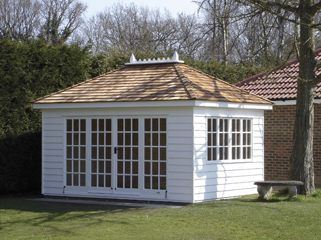 "<p id=""boldtitle"">Hip Roof Summerhouse</p>14' x 10' (4270mm x 3050mm) hip roofed summerhouse.  Shown with optional cedar shingles tiles and ridge finial.  Painted white.<br/>"