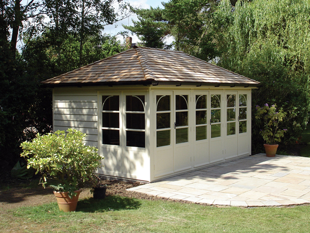 "<p id=""boldtitle"">Hip Roofed Summerhouse<br/></p>16' x 10' (4880mm x 3050mm) hip roofed summerhouse.  Shown with optional window design, cedar shingle tiles and guttering.  Painted cream.<br/>"