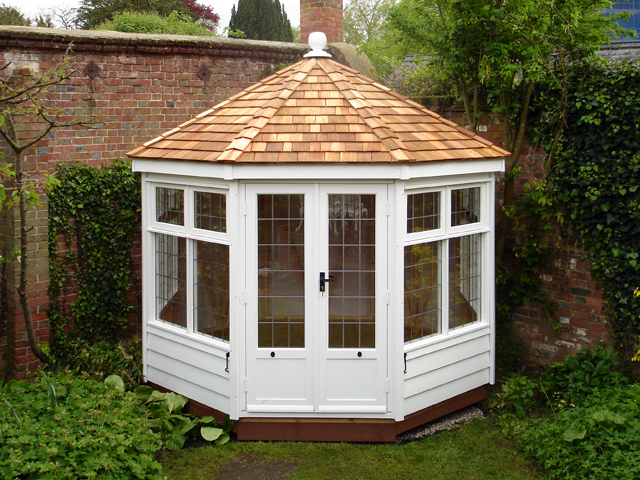 "<p id=""boldtitle"">Hip Roofed Summerhouse</p>10' x 10' (3050mm x 3050mm) hip roofed octagonal summerhouse.  Shown with optional square leaded windows, cedar shingle tiled roof with ridge finial and painted white.<br/>"