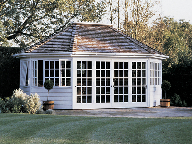 "<p id=""boldtitle"">Hip Roofed Octagonal </p>18' x 14' (5490mm x 4270mm) hip roofed octagonal summerhouse.  Shown with optional cedar shingle tiles, ridge finial, white box guttering and down pipe.  Extra doors and windows.  Painted white.<br/>"