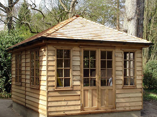 "<p id=""boldtitle"">Hip Roofed Summerhouse</p>Hip roofed summerhouse.  Shown with optional cedar shingle tiles.  Treated in our standard medium brown preservative.<br/>"