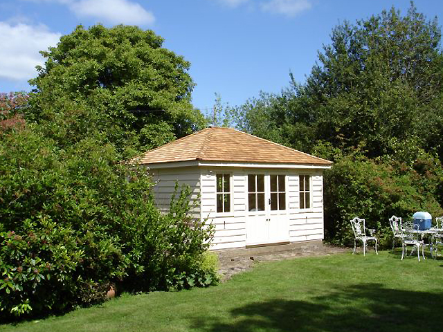 "<p id=""boldtitle"">Hip Roofed Summerhouse<br/></p> 12' x 8' (3660mm x 2440mm) hip roofed summerhouse.  Shown with optional cedar shingle tiles and painted white.<br/>"
