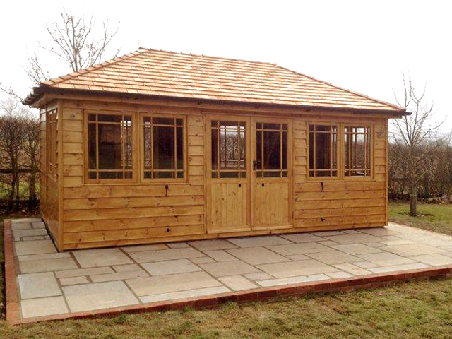 "<p id=""boldtitle"">Hip Roofed Summerhouse</p>Hip roofed summerhouse.  Shown with optional design windows/doors, cedar shingle tiles and stained.<br/>"