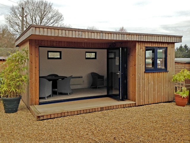 "<p id=""boldtitle"">Kent Studio</p> 16' x 12'8"" (4880mm x 3860mm) including decking area.  Thermowood cladding.  Polyester powder coated aluminium bi-folding doors shown open.<br/>"