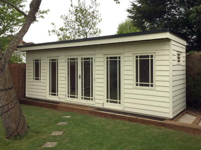 "<p id=""boldtitle"">Corner Shaped Garden Room</p>7m x 6 8m Corner Shaped Garden Room with partition at the back for storage.<br/>In prepared weatherboard cladding - painted. <br/>Used as an additional playroom.<br/>Double glazed/insulated and plastered interior.<br/>Made to order."